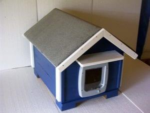 Vista de una casita azul para gatos de exterior